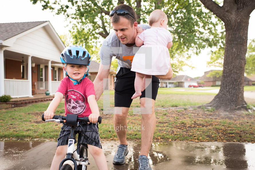 a father teaching his son to ride a bike
