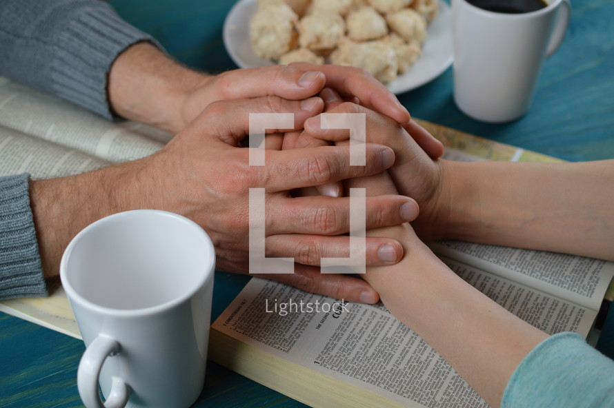 couple holding hands praying over open Bibles