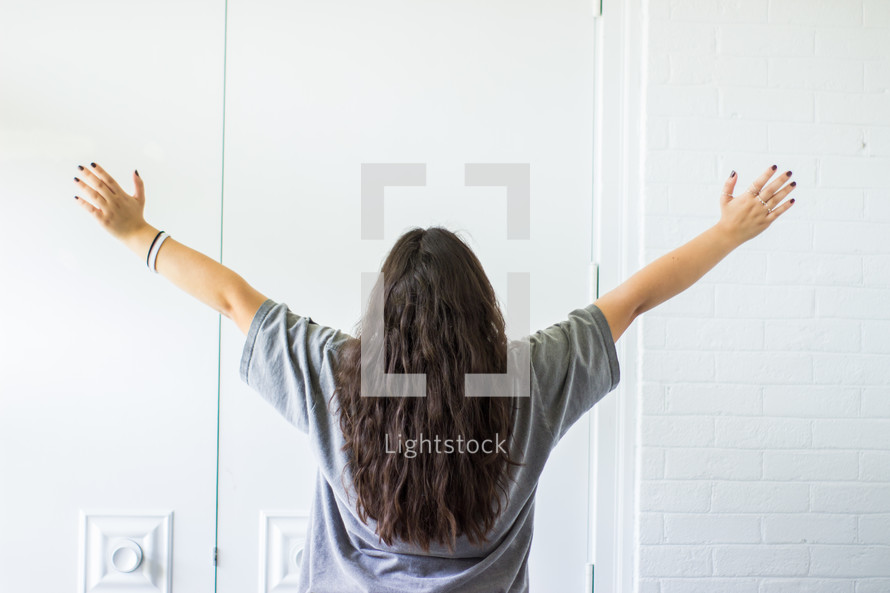 teen girl with arms raised