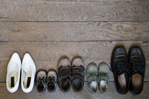 Family's shoes lined up on a wood floor.