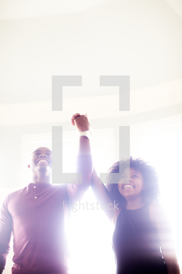 celebration, man, woman, African American, raised hand, holding hands, love, triumphant, victorious, marriage, love, joy, united, smiling, happy, glow