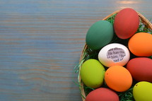 a white eggshell with a piece of the bible inside saying: HE HAS RISEN! between colorful painted eggs in a basket