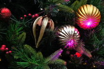 Red, gold and purple ball ornaments hanging from Christmas tree