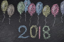 chalk balloons on slate with the number of the year 2018