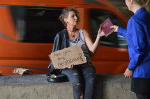 a woman sitting under a bridge with bottle of alcohol holding a sign and receiving a bible from a businesswoman