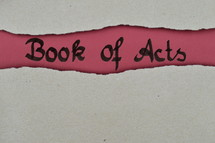 Book of Acts - torn open kraft paper over dark red paper with the name of the book: Acts of the Apostles