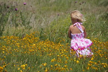 Young girl standing in field with flowers