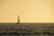 little sailboat sailing on the wide ocean in the yellow light of sundown.