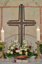 Cross, candle sticks and a flower arrangement on an altar. 