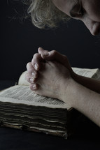 a woman praying over the pages of a Bible