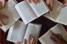 Hands holding bibles in different languages open at 2 kings 15.