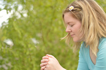 Young blonde woman praying outdoors. 