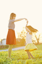Mother and daughter dancing on a spring day.