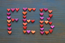 The word FEB for February written with many little colorful clay hearts on cyan wooden background