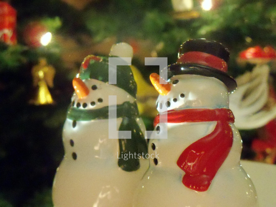 A pair of snow people snow men smile as they take in the Christmas lights of a lighted Christmas tree surrounded by CHristmas lights to celebrate the Spirit of the Christmas holidays.