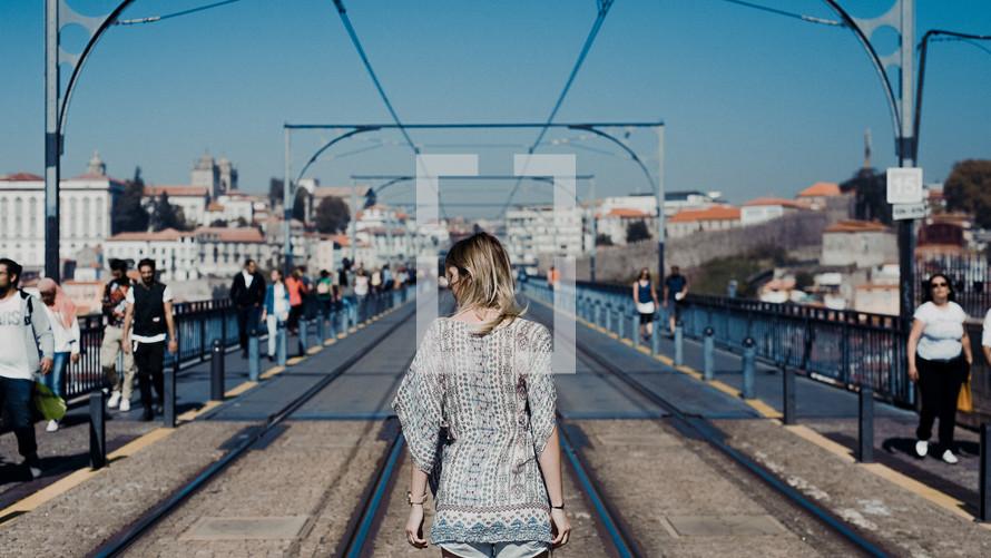 woman walking on electric rail tracks