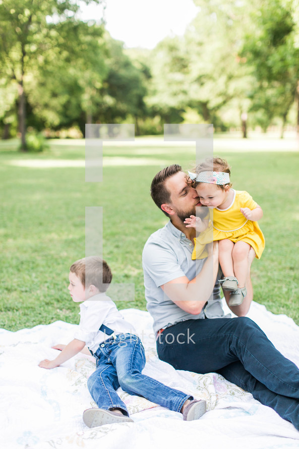 a father sitting on a blanket in the grass with his kids