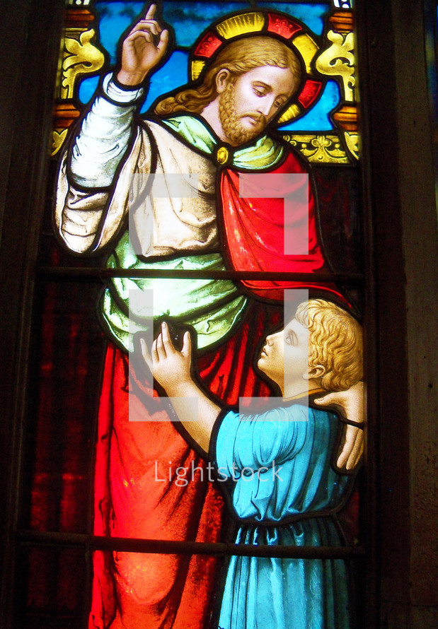 A stained glass window of Jesus and child  together as Jesus points to Heaven. Beautiful stained glass window with red, blue, gold, yellow colors. Jesus said 'Suffer the little children to come unto me' as it takes the faith of a child to believe and trust in Christ for eternal salvation.