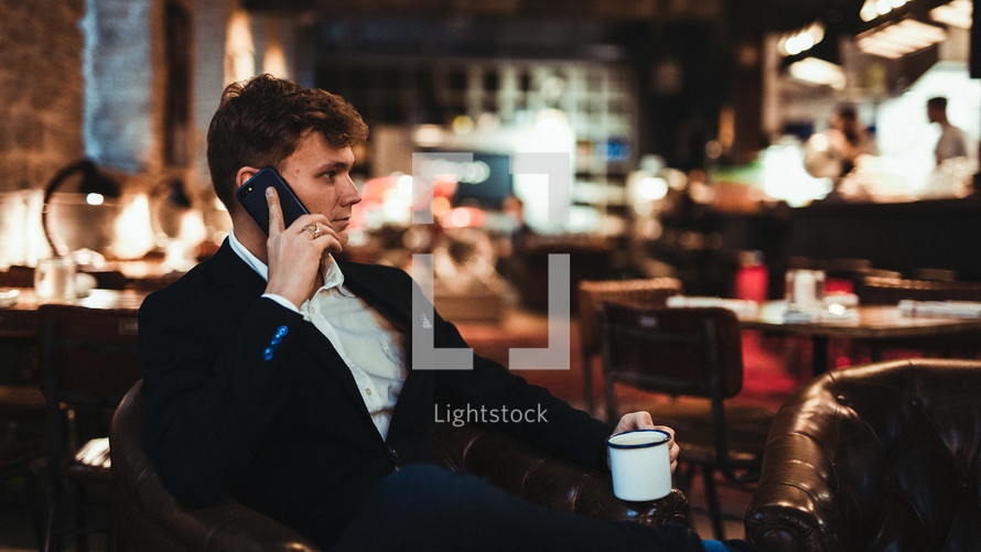 a man sitting alone at a table at a restaurant talking on a cellphone