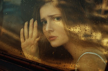 face of a woman looking through a car window