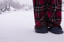 Man with slippers and pajamas standing in snow