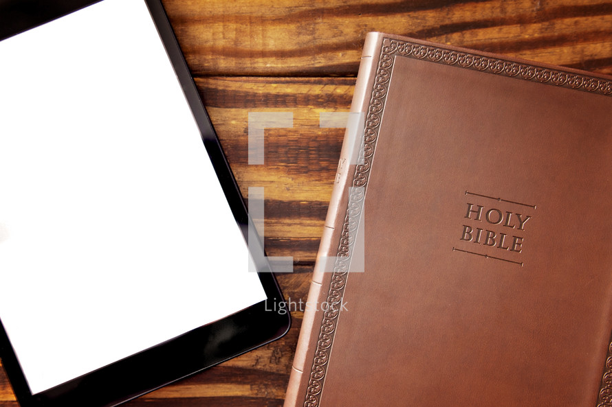 tablet and Bible on a wood desk