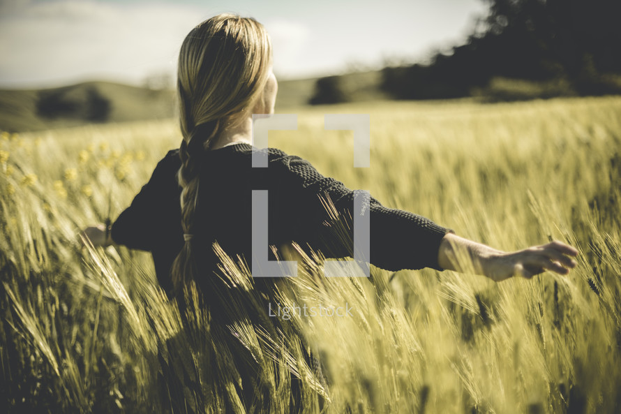 a woman with outstretched arms standing in a field of wheat