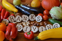 fruits and vegetables with burned wood showing the word thanksgiving.