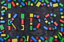 the word KIDS out of colorful wooden toy blocks on black wooden background with frame out of toy blocks