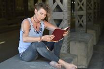 homeless woman reading a Bible under an overpass
