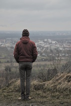 a man standing on a hill looking into the valley