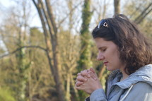 a woman in prayer outdoors