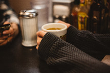 a woman in a sweater holding a mug of coffee