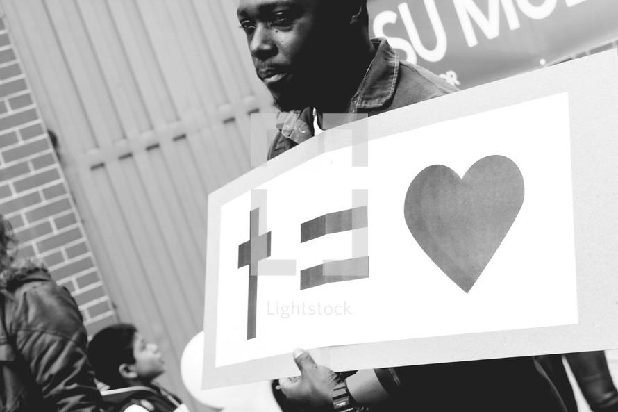 A man holding a sign cross = heart