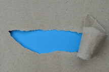 ripped paper revealing blue blank space for words