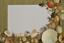 blank paper, and seashells on a beach mat