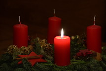 One candle is burning at the Advent wreath for the first advent. 