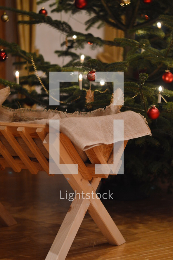 a manger in front of a Christmas tree