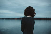a woman with her back to the camera looking at lake water