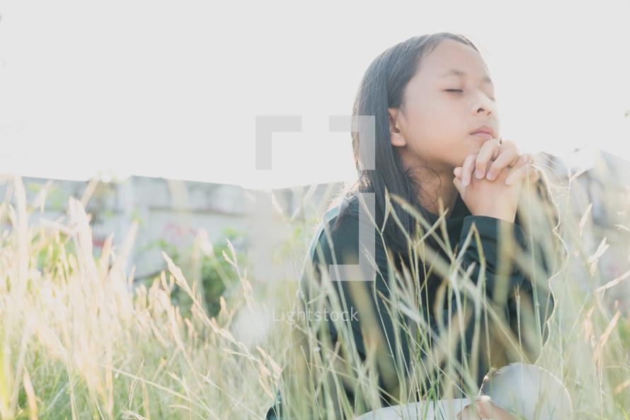 girl praying in a field