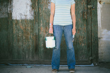 Woman standing in front of old wooden wall holding paint can and paint brush