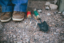 Person's feet and garden tools on a rocky ground