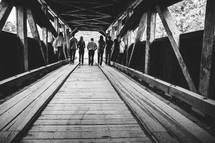 teens walking on a covered bridge