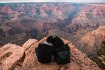 a man and woman sitting at the edge of a cliff looking out at canyons snuggling