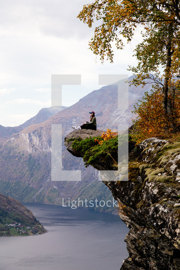 a woman sitting at the edge of a cliff looking out at the view