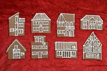 eight different self baked gingerbread house fronts with numbers on them on red velvet as part of an advent calendar