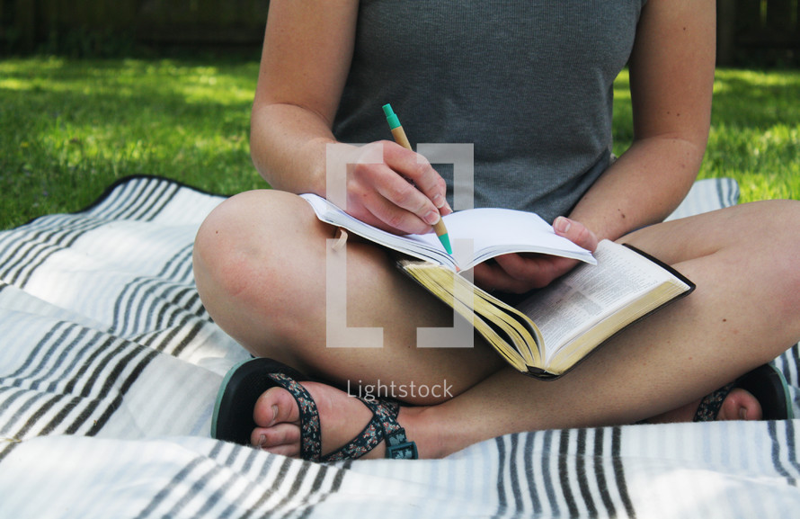 a girl sitting on a blanket in the grass reading a Bible and writing in a journal