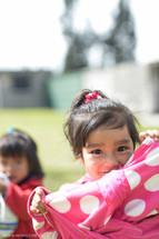 A smiling little girl in a polka dot dress.