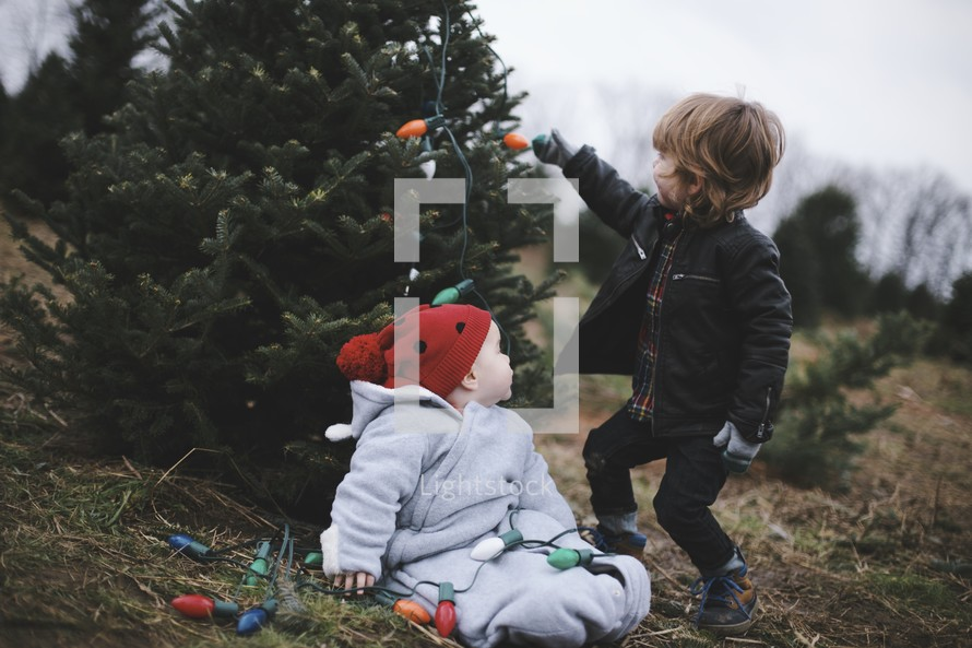 toddler and infant in a Christmas tree lot with Christmas lights