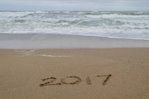 tide washing onto a shore with the year 2017 in the sand